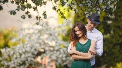 Young man and woman couple in a blooming apple garden. Tender holding each other. Spring lovestory. Brown-haired girl with long hairs. Young family